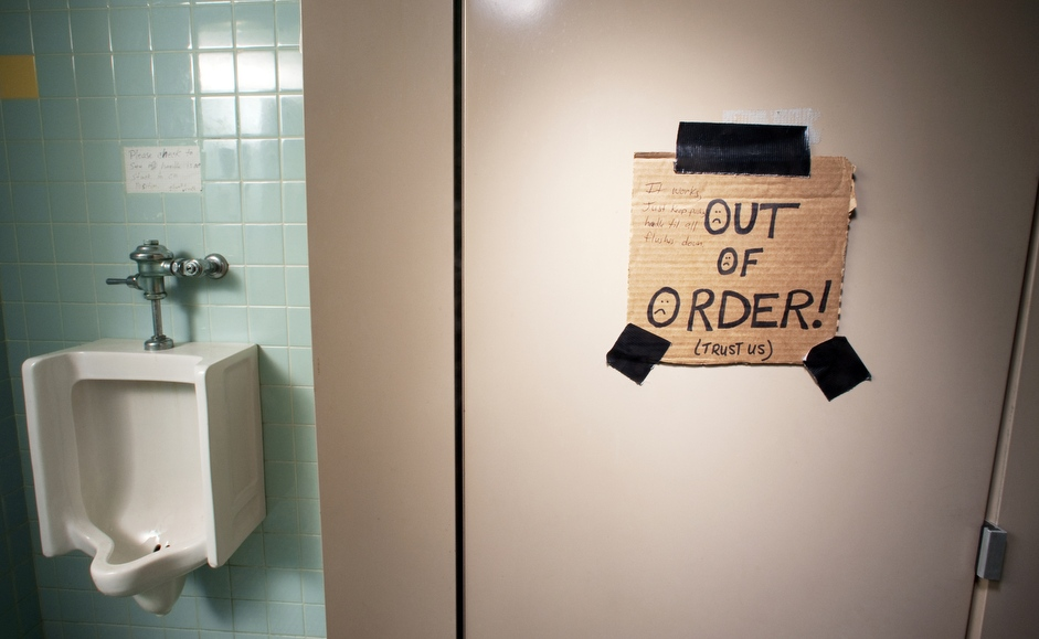 """a broken toilet stall indicated by a handmade sign reading """"Out of Order (Trust Us)."""""""