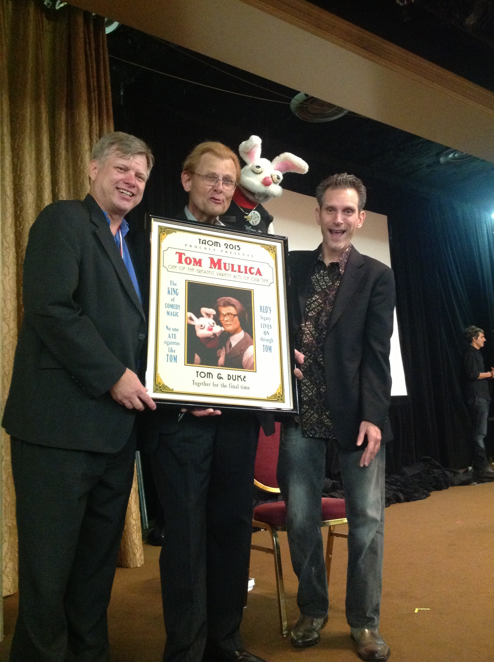 Tom Mullica accepts special poster from Mark Jensen and Chip Romero