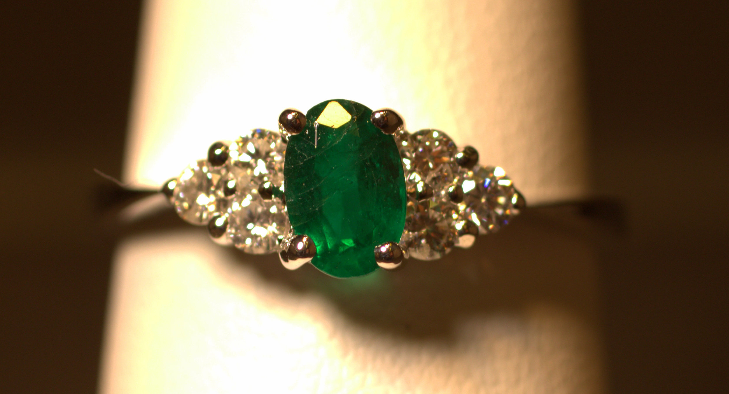 6 diamond and1emerald ring. The oval emerald has 3 diamonds on either side. Thesebright white diamonds accentuate the nice darker green emerald. This piece is made in white gold and is a great modern take on a classic 3 stone ring.  $1350