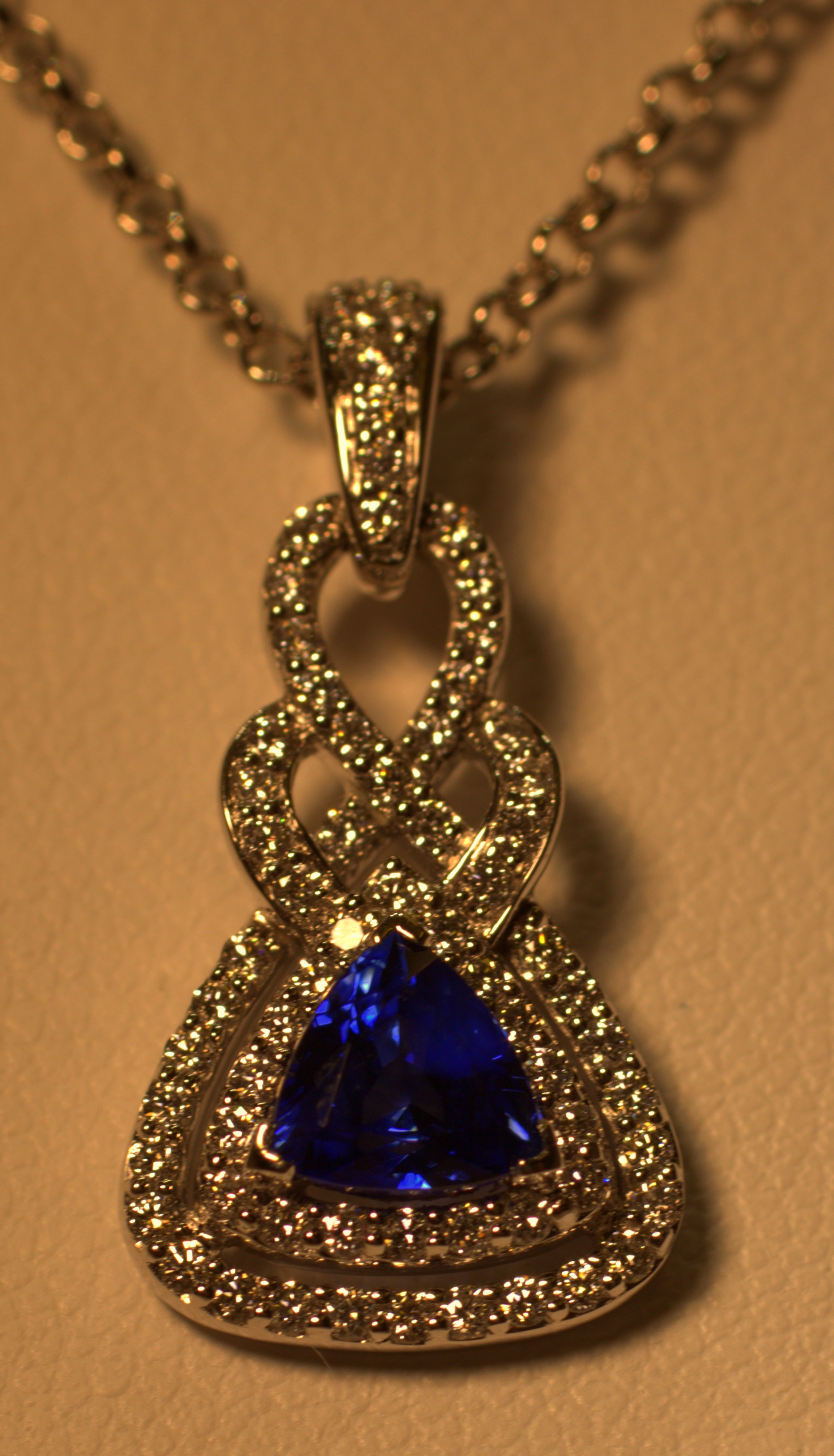 Vibrant blue sapphire and diamond pendant. This pendant has a beautiful blue sapphire that sparkles almost like a diamond. It has an ideal blue color with an intricate diamond twist just to bring out the glisten in the gemstone. This piece will be an eye catcher from across the room.  $3500