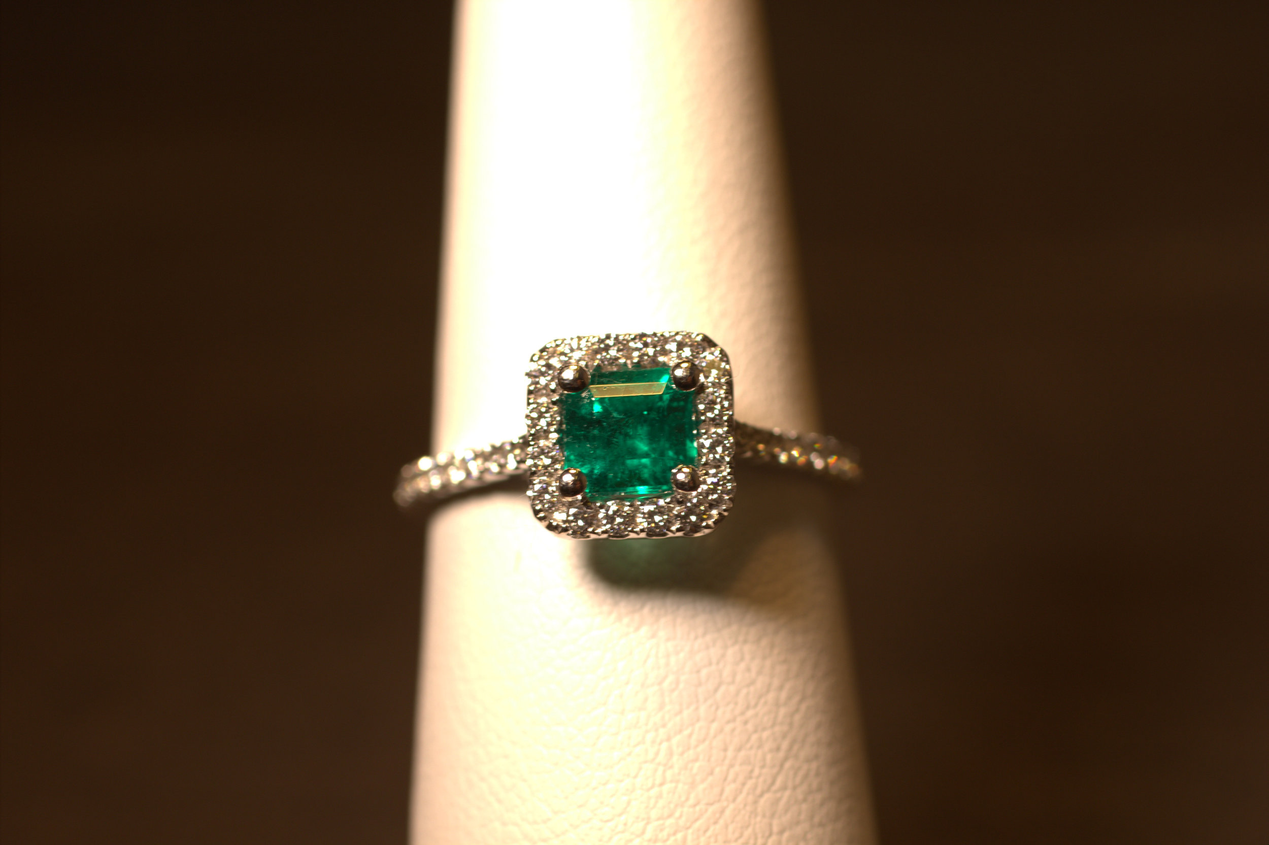 Platinum and diamond emerald ring. Square emerald cut emerald in a diamond halo with diamonds down the shank. Beautiful Columbian emerald displays rich green hues even throughout the stone. The emerald is set low into the halo to protect the gemstone. Great green color, the color of the year.  $6000
