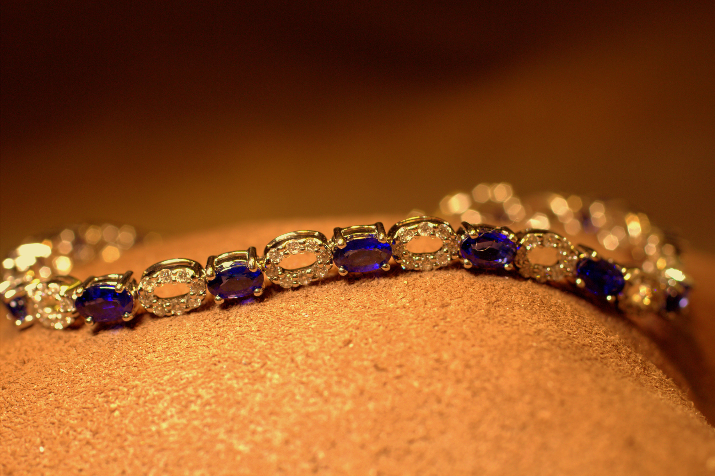 Classic styling with a twist oval of diamonds between each sapphire set in white gold.  $6000