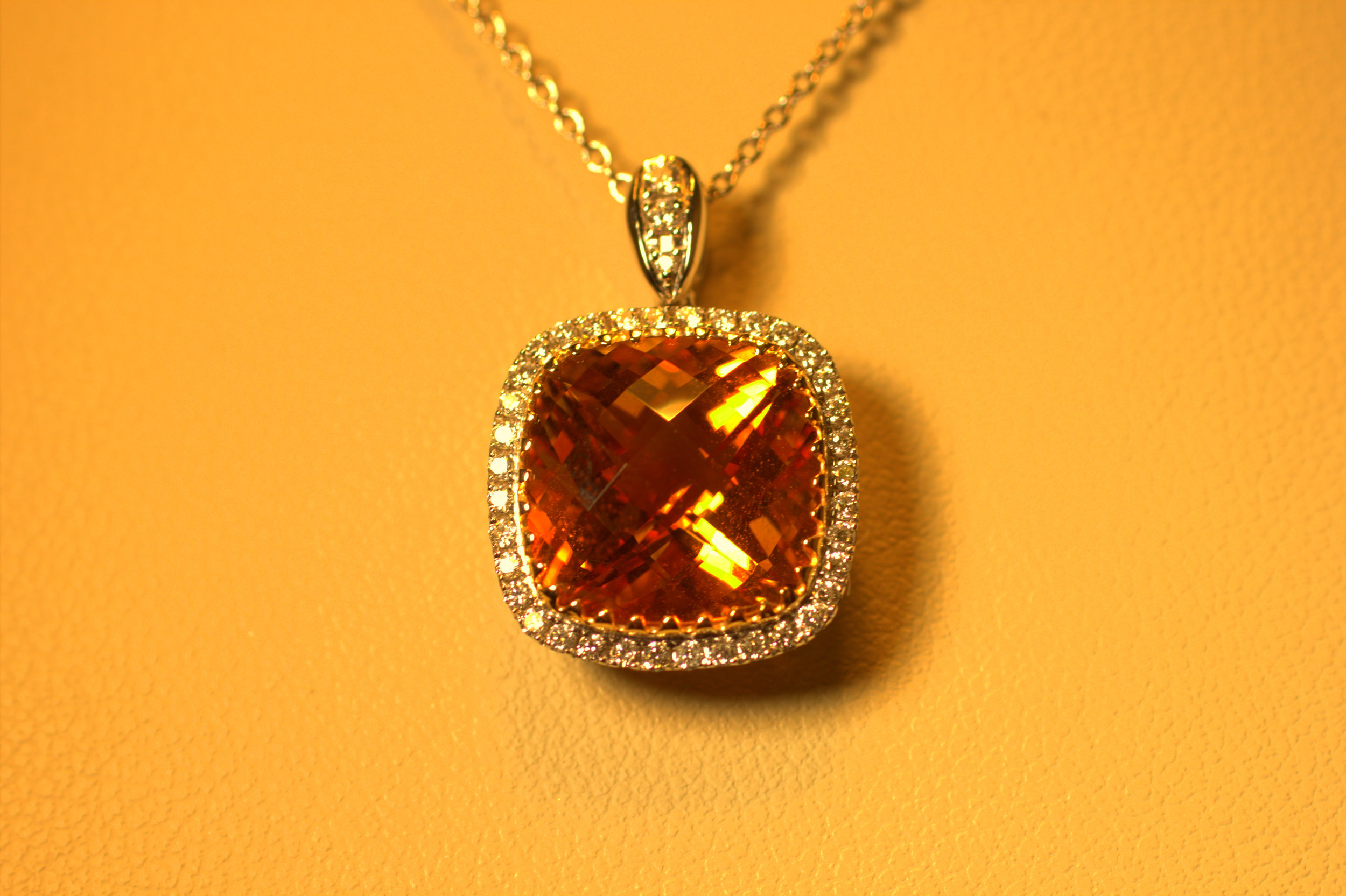 Classic citrine pendant set in yellow gold with a diamond halo set in white gold creating a beautiful rich orange color in the citrine diamond. Adjustable chain.  $2250