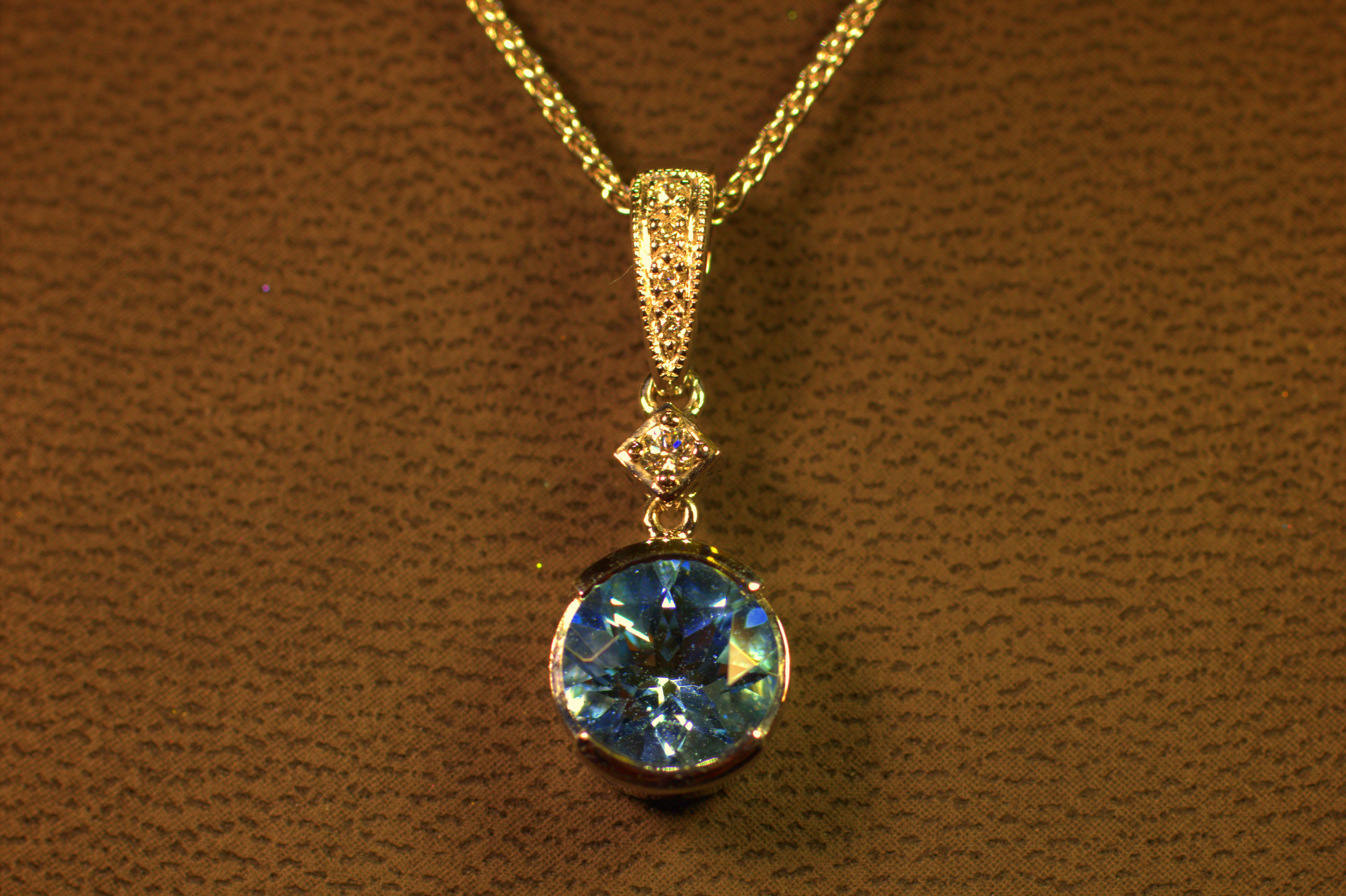 Half bezel pendant with beautiful aquamarine stone. Great fire diamond bail and a single diamond allows for lots of movement and big sparkles. Displayed on white gold chain.  $1150