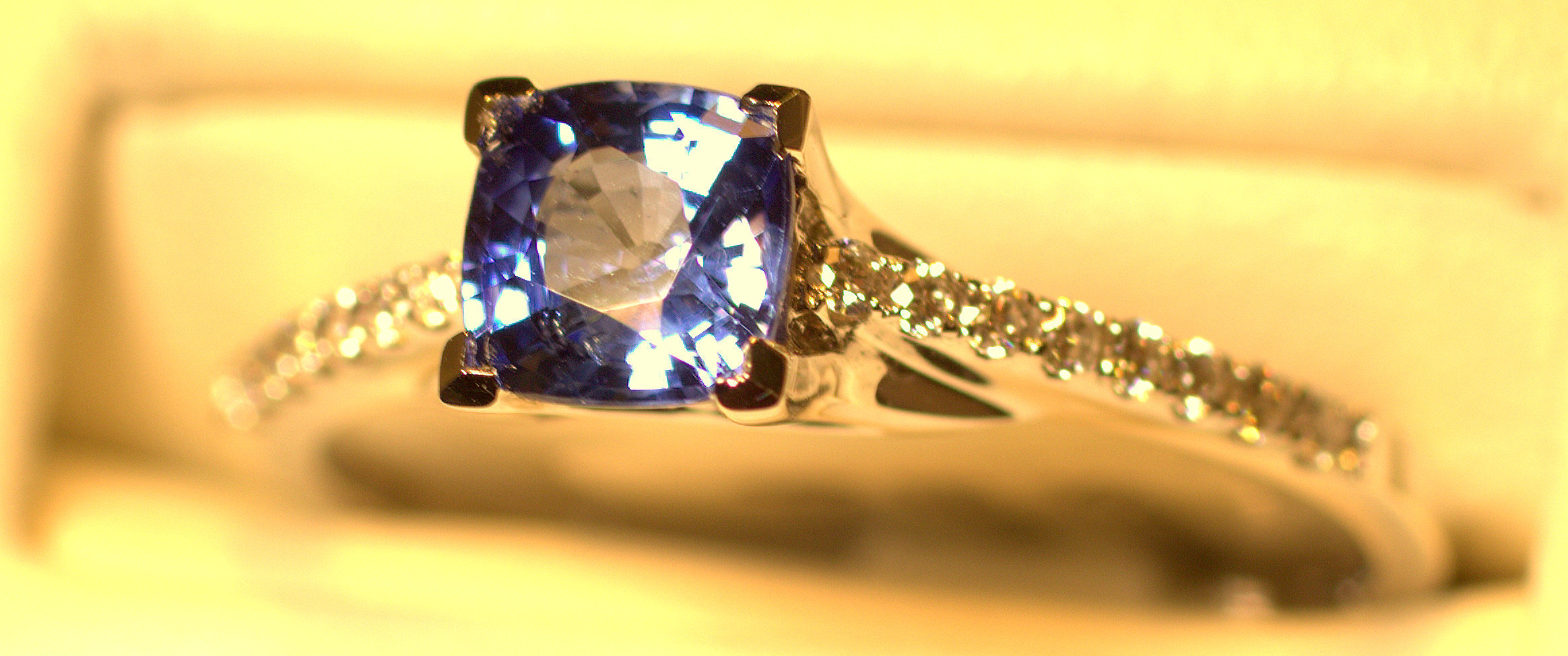 Light blue sapphire and diamond ring. Beautiful square cushion-cut sapphire set with diamonds down either side.  $1350