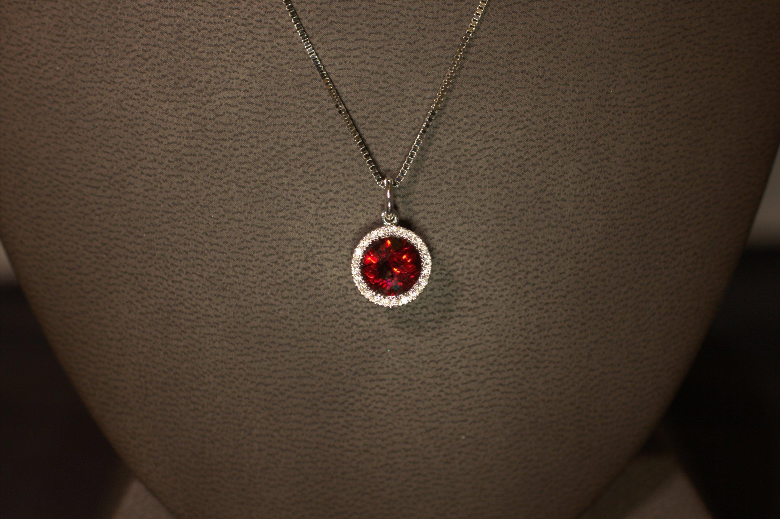 Modern styling vintage diamond halo surrounds a beautiful garnet. Ideal cut diamonds provide incredible sparkle.  $925