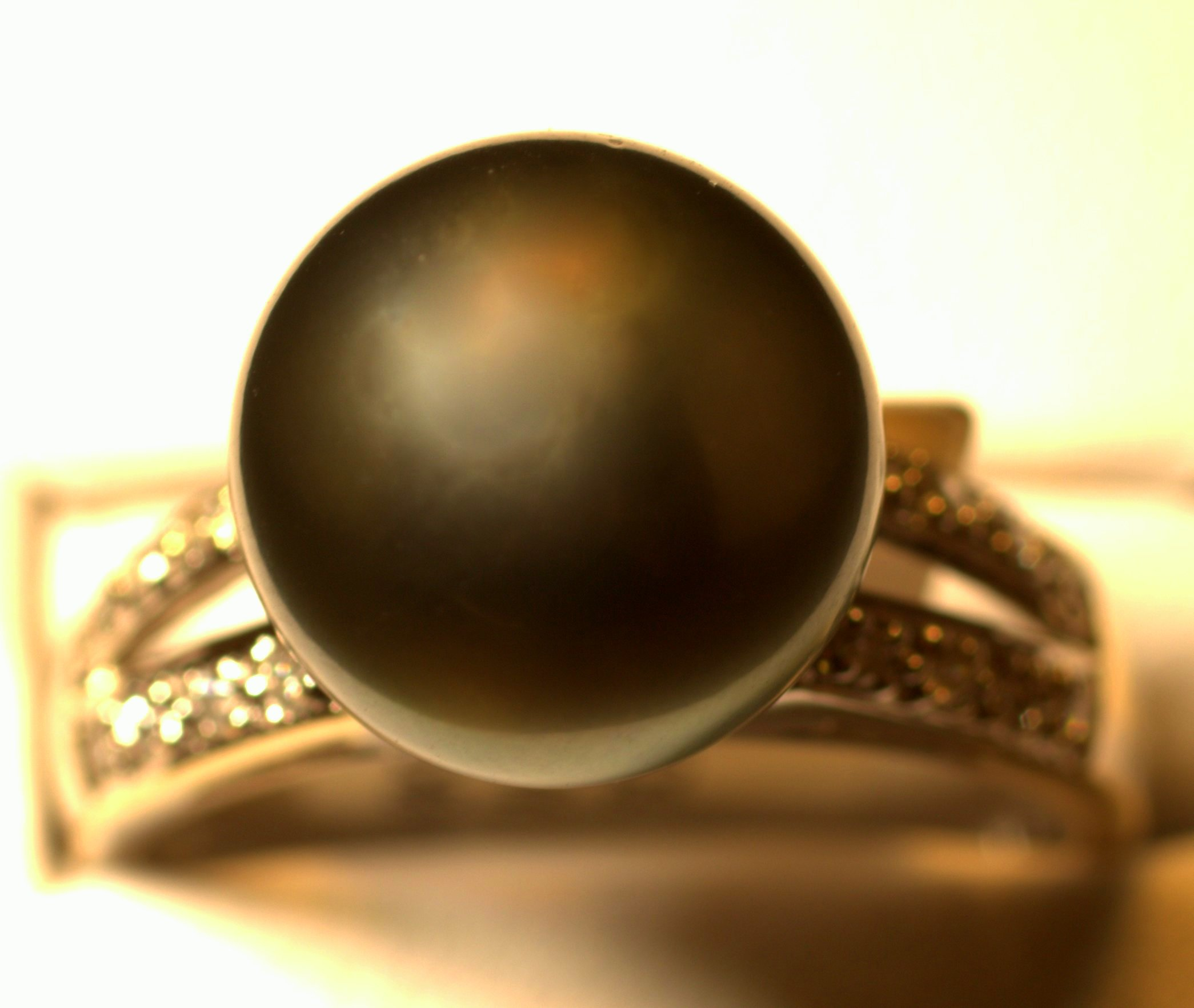 Natural black Tahitian pearl ring with diamond split shank. Bright white diamonds accentuate the great luster of the black pearl.  $1500