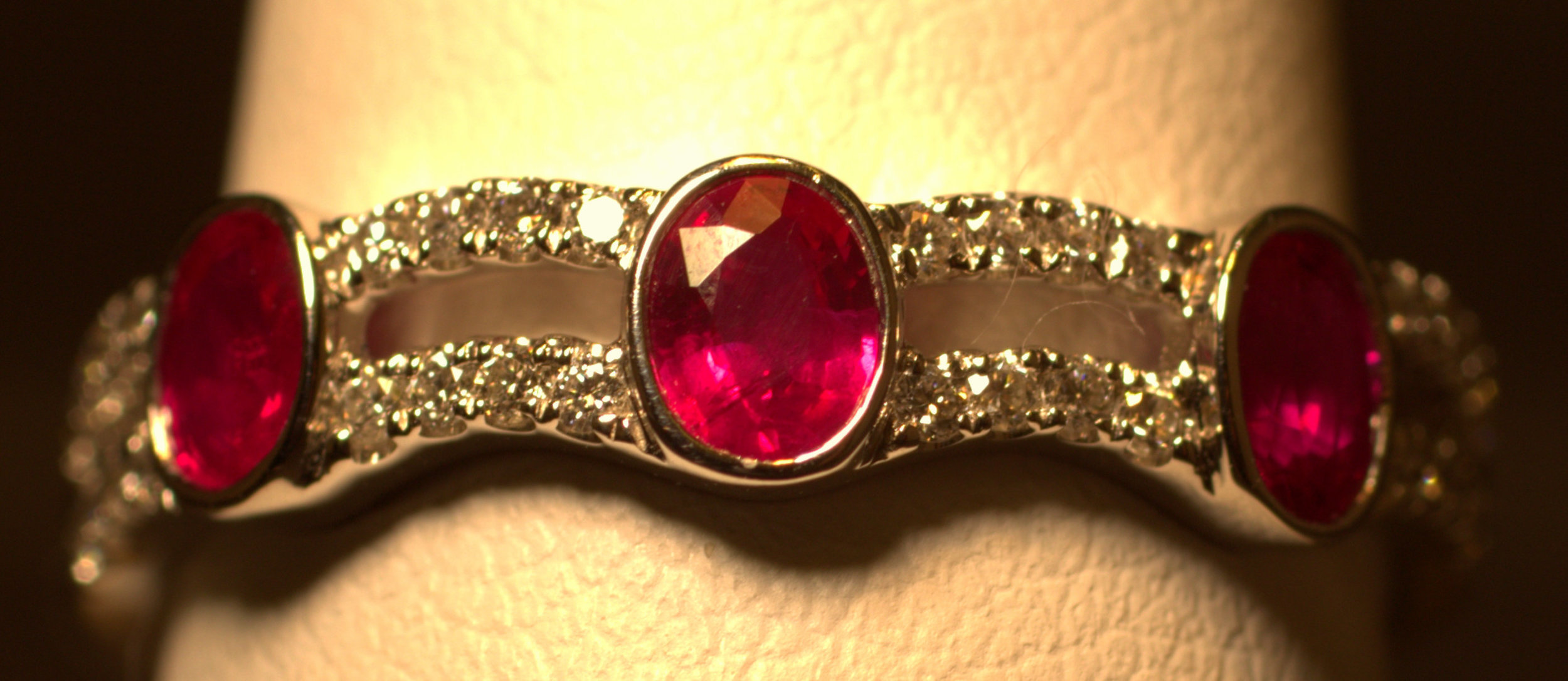 Ruby and diamond ring two rows with two of diamonds between oval rubies.  The rich, red color of the rubies are set off by the sparkle of the well cut diamonds.    $1750