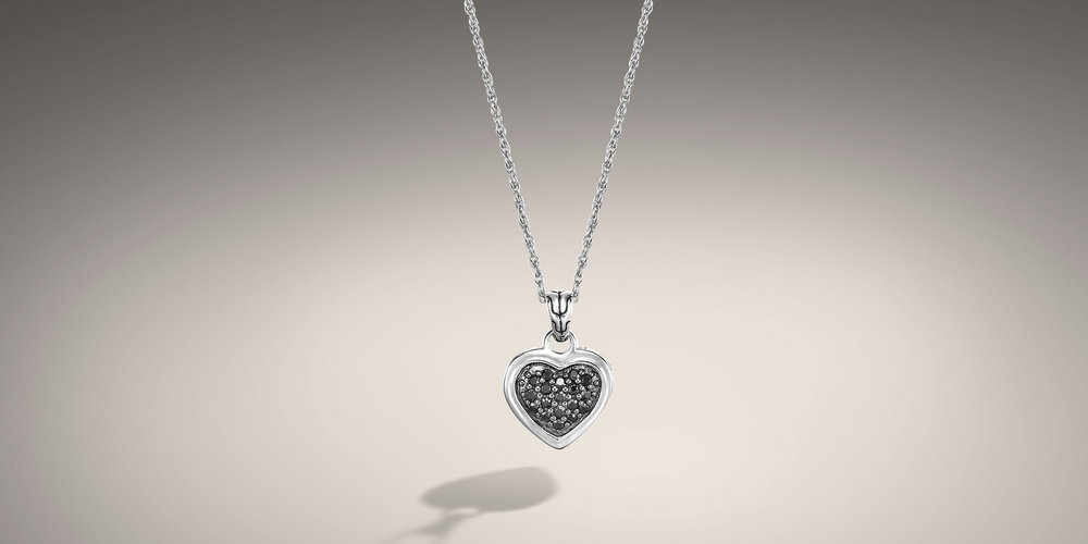 John Hardy black sapphire pave heart pendant. The pendant sits on an 18 inch link chain. The heart has hand woven silver around the outside and 18 pave set black sapphires in the center.