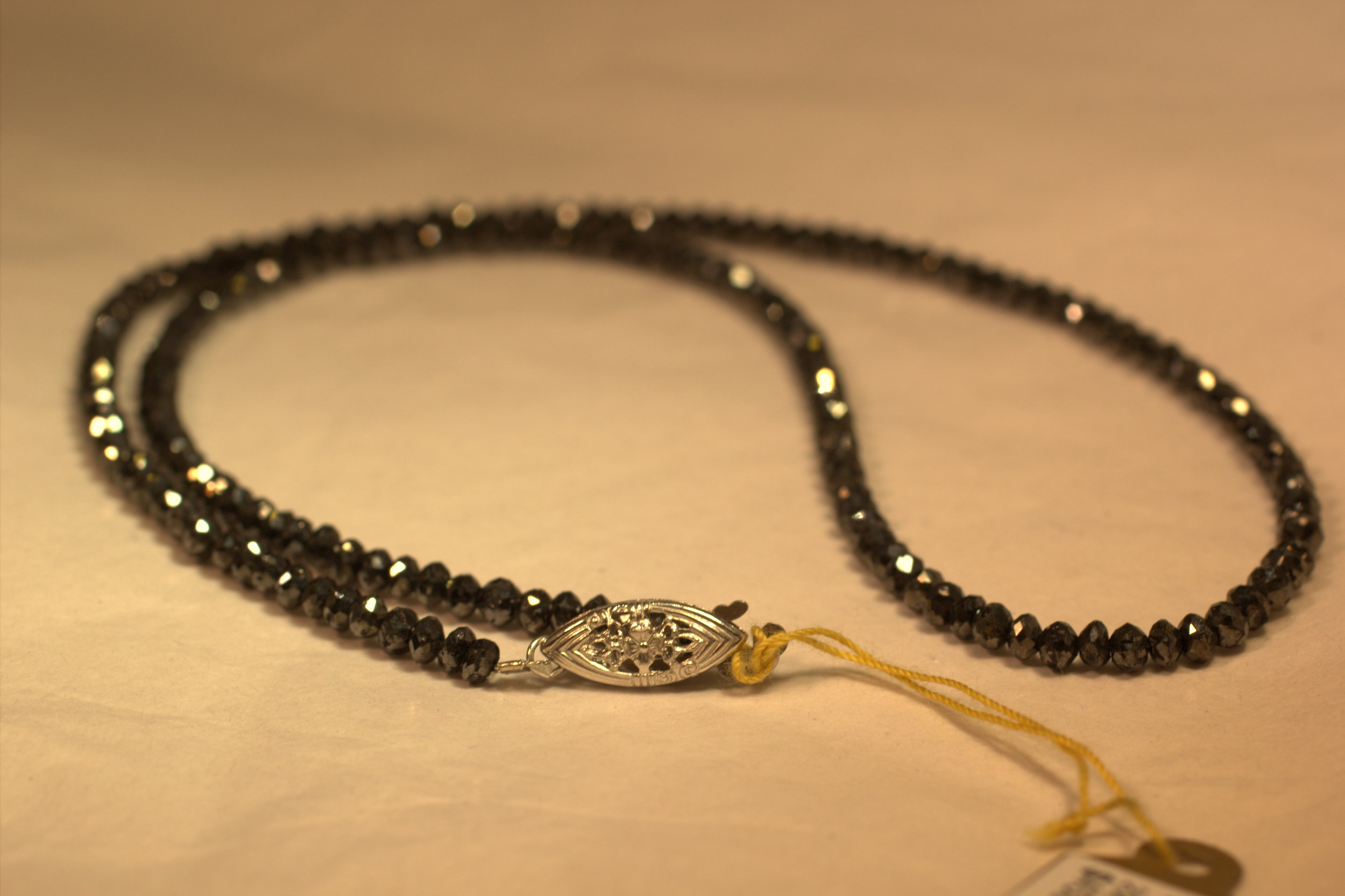 20 carat black diamond strand. The strand faceted and drilled black diamonds strung together with a 14 karat white gold clasp. The diamonds are all partially faceted and sparkle more than any other black stone.
