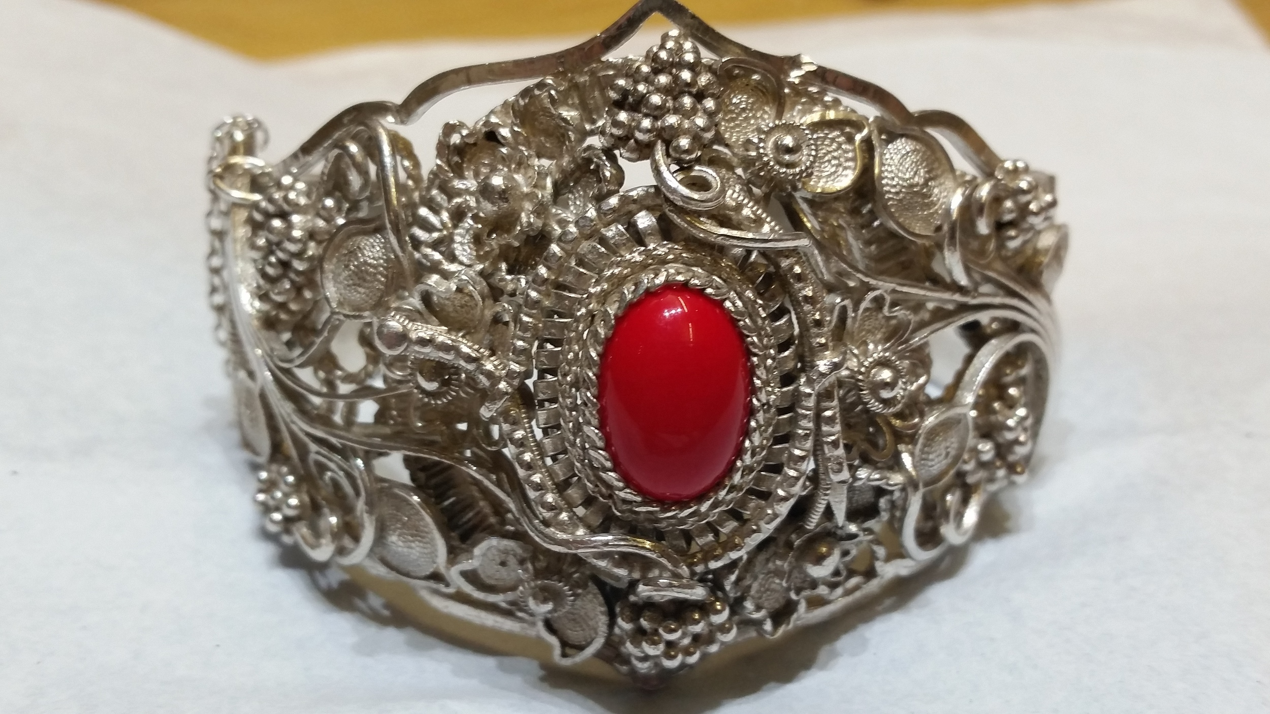Handmade in Yugoslavia this bracelet features local flower and grapes carved into and coming off the silver bangle bracelet. The center stone is a Carnelian or a red onyx. This unique estate piece is a work of art.    $400