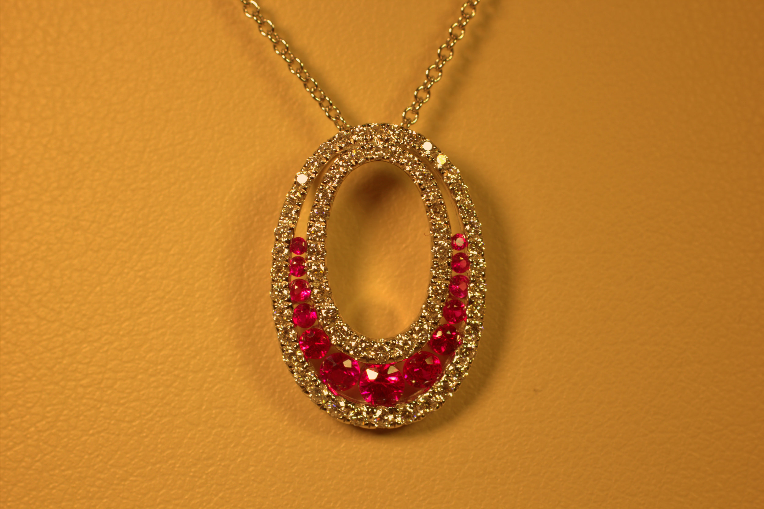 Beatuiful pigeons blood red ruby pendant in oval circle of diamonds set betweeen two rows of ideal cut brilliant bright diamonds rubies are july birthstone chic modern available at marlen jewelers in rocky river minutes from cleveland.jpg