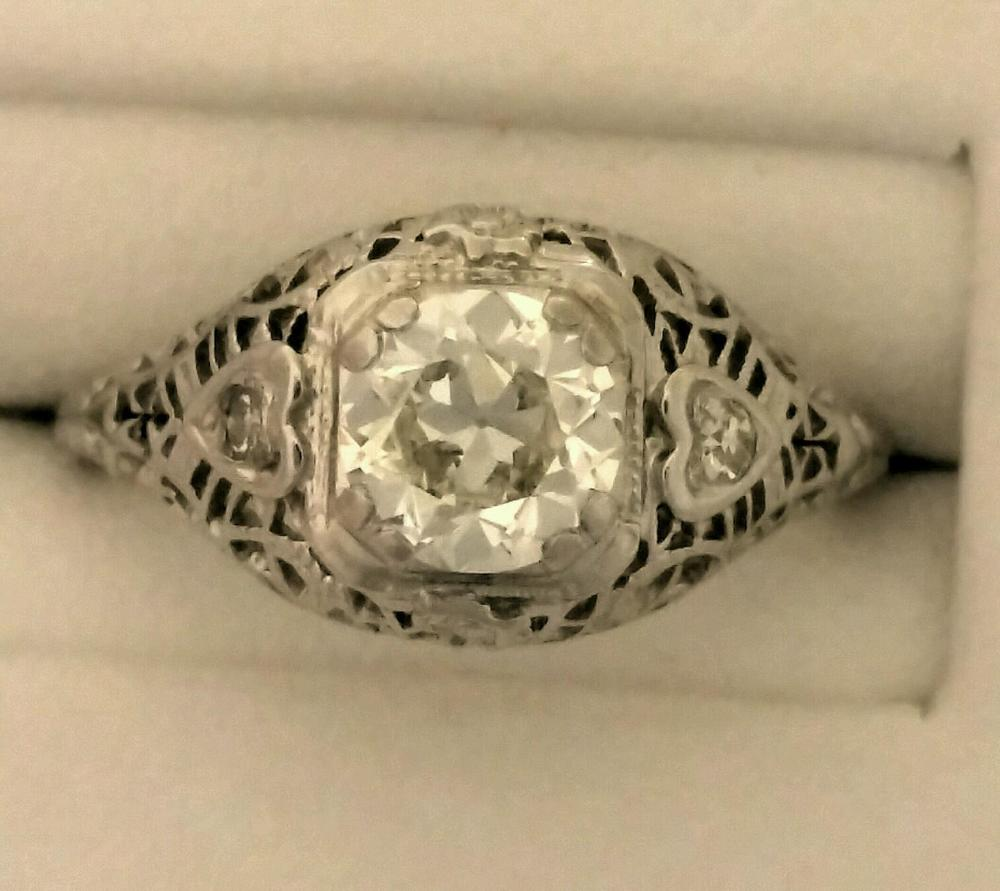 One diamond engagement ring fashioned in 18 karat white gold. The filigree style mounting has one old mine cut diamond 4 double prong set in the center. The diamond measures 5.8-5.82 x 3.55MM and weighs 0.71 with J color and WS clarity. One round diamond is set into heart shape filigree on each side. Two diamonds total 0.05 carat. Price $3,200
