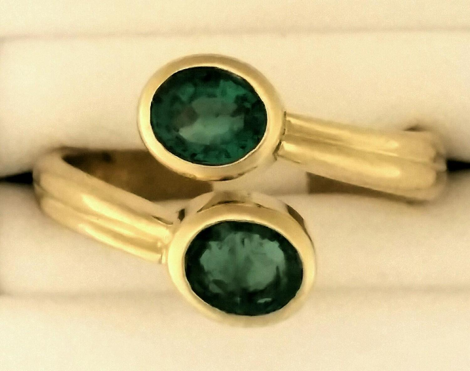 Bezel set, oval emeralds adorn this 18K gold ring