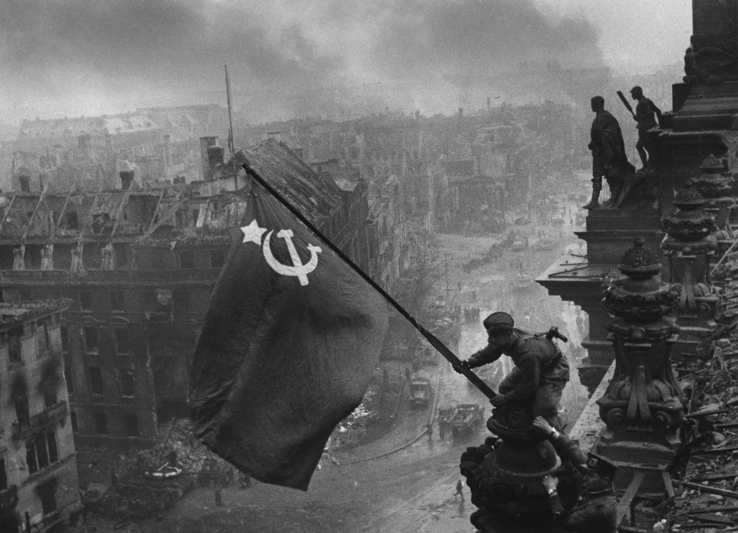 Soviet soldiers raise the hammer and sickle over the Reichstag during the Battle of Berlin on May 2nd, 1945. Photo credit:  creative commons.
