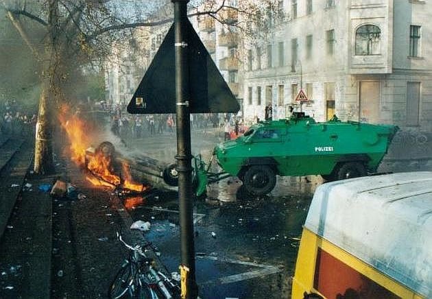 A still-burning car after riots in Berlin. The stairs on the left of the photo lead to Mariannenplatz. Photo credit:  creative commons.