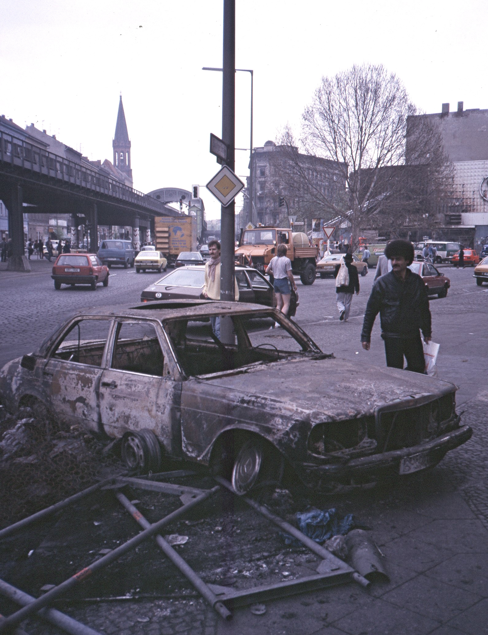 A burned-out car on the streets of Berlin on the morning of May 2, 1987. The photo was taken in the Kreuzberg district at the intersection of Skalitzerstraße and Mariannenstraße. The train station in the background is Görlitzer bahnhof, today a stop on the U-1 line. Photo credit:  creative commons.