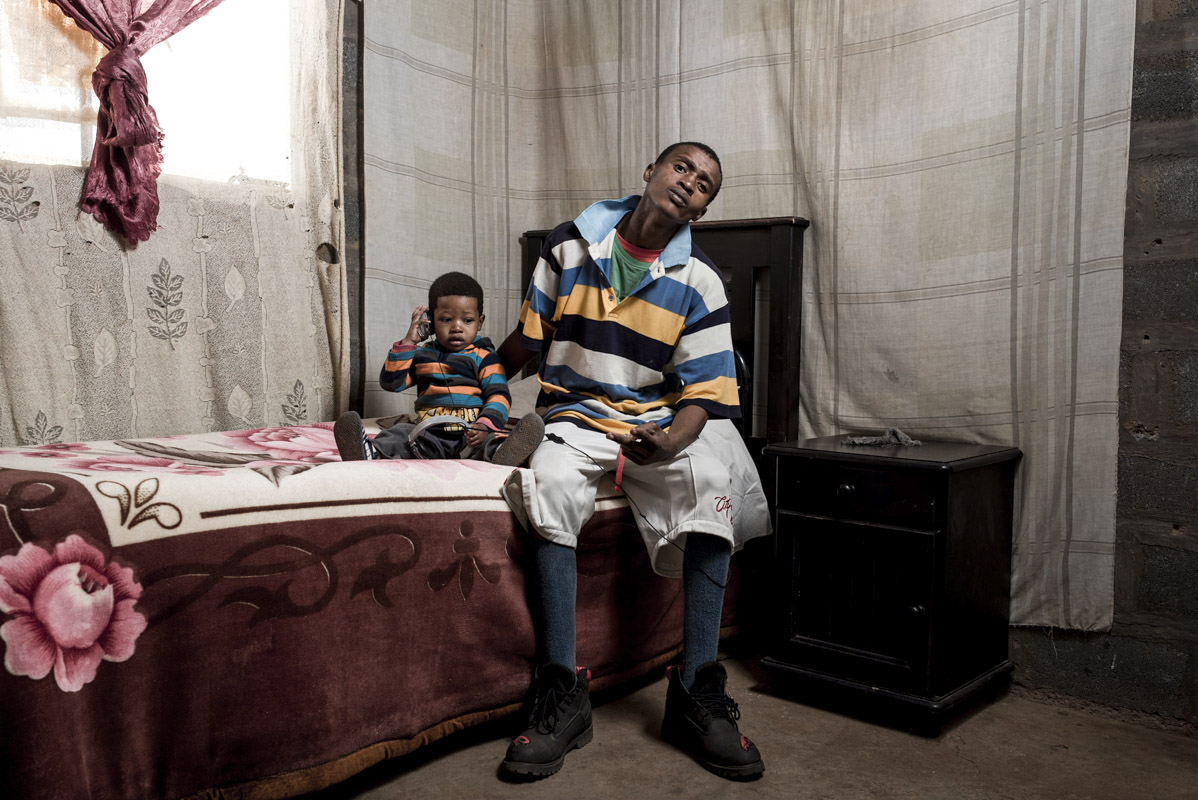"""Andre """"Bushy Bird"""" Ntholo at home with his son."""