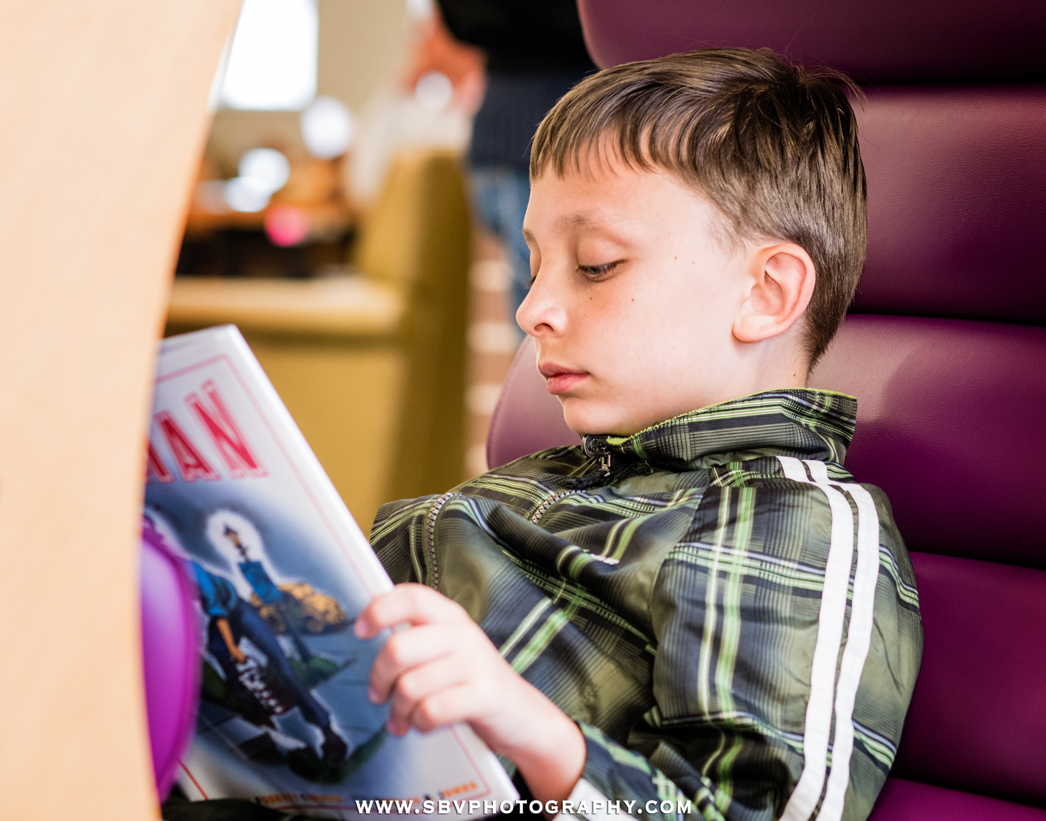 In this event photography photo, a child reads his graphic novel while attending the grand opening of the Griffith Library in Northwest Indiana.