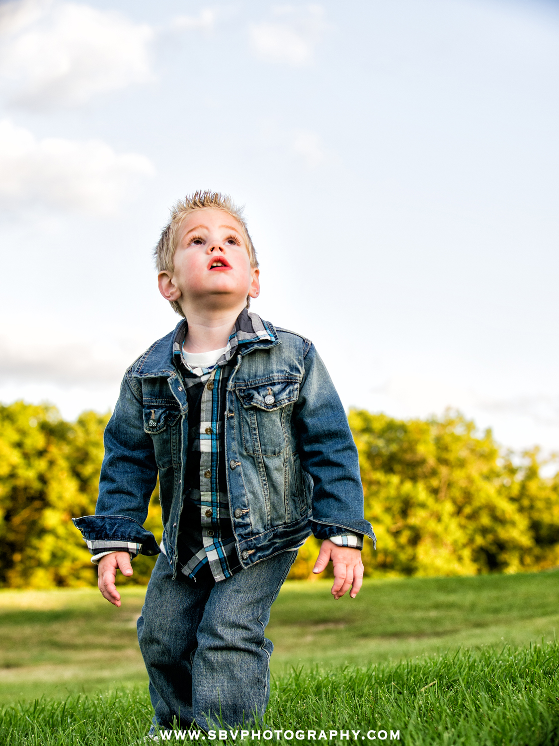 a little boy looks up toward the sky in wonderment as he is captured during a Lifestyle Portrait Session in Griffith, Indiana.