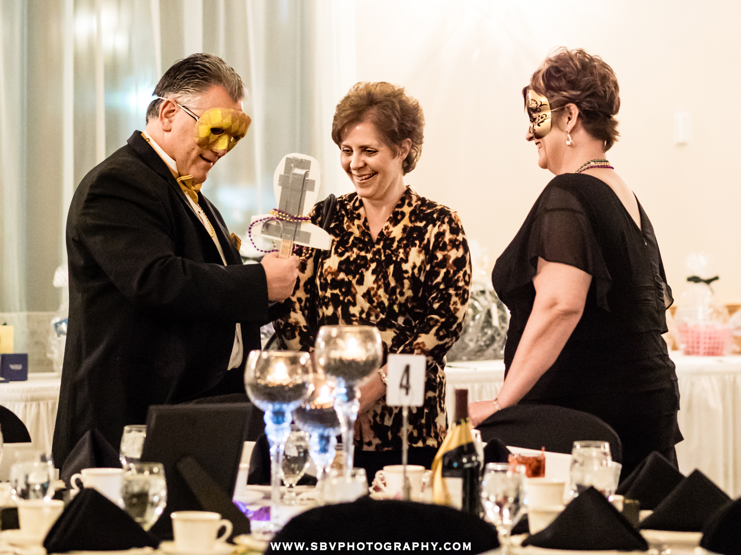 Guests at a Masquerade Ball share a laugh as they show each other their costume props.