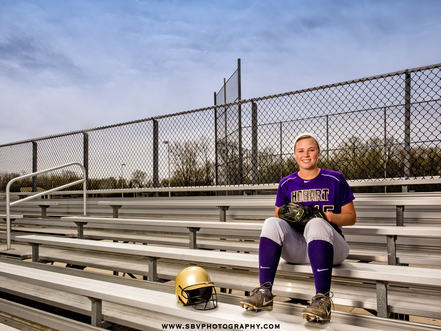 Senior girl from Hobart High School poses on the bleachers at the baseball field.