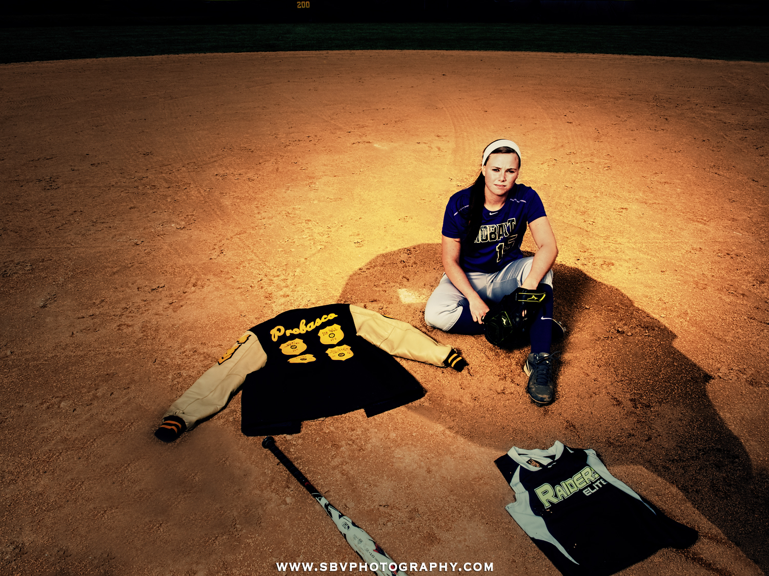 Hobart high school third base player poses for her senior picture on the pitcher's mound.