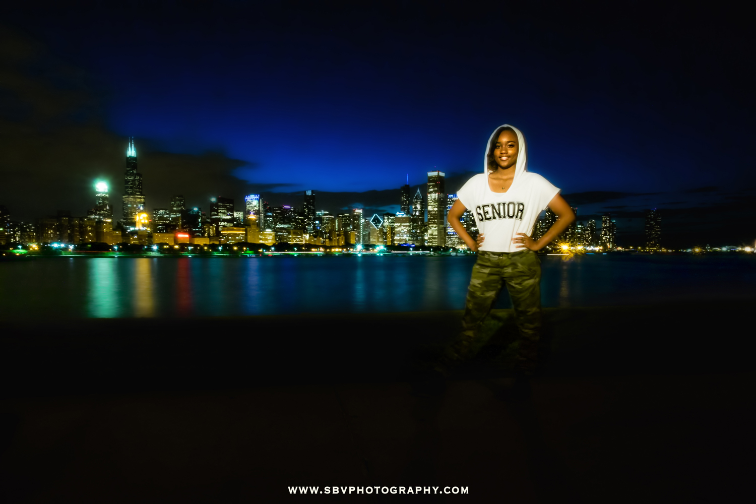 A 2015 high school senior poses in front of the Chicago Skyline at night.