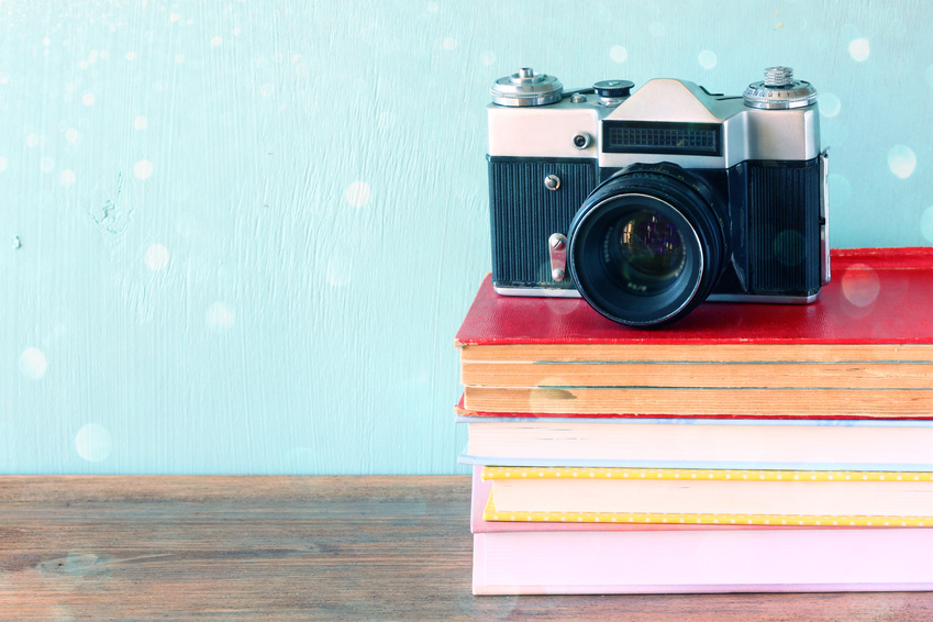 Vintage camera on a stack of library books.
