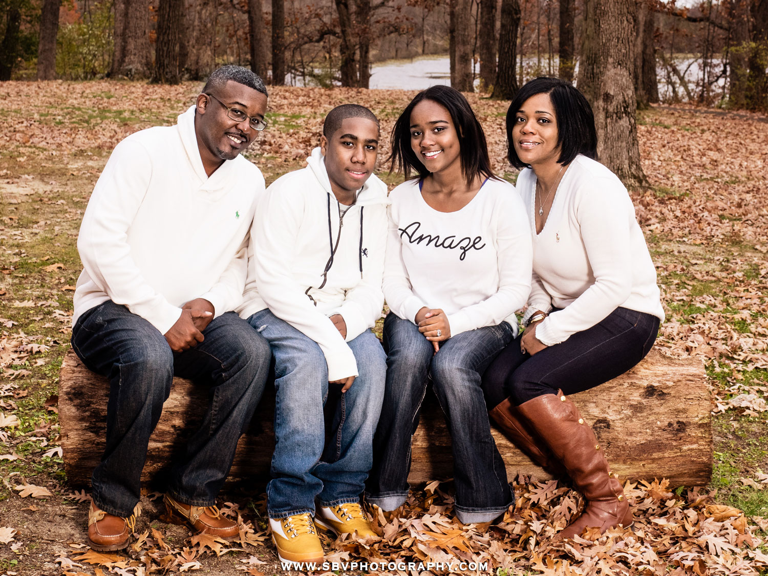 A family poses for an Autumn family picture atop a downed tree.