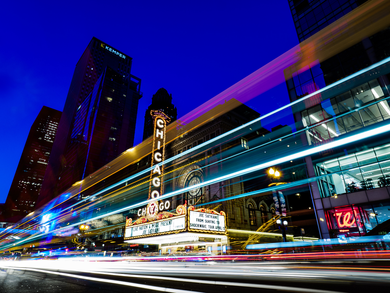 Chicago Theater at night with traffic blazing by.