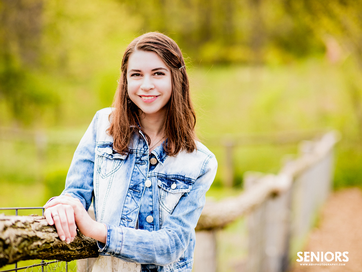 Senior photo at an old rustic fence at Taltree Arboretum.