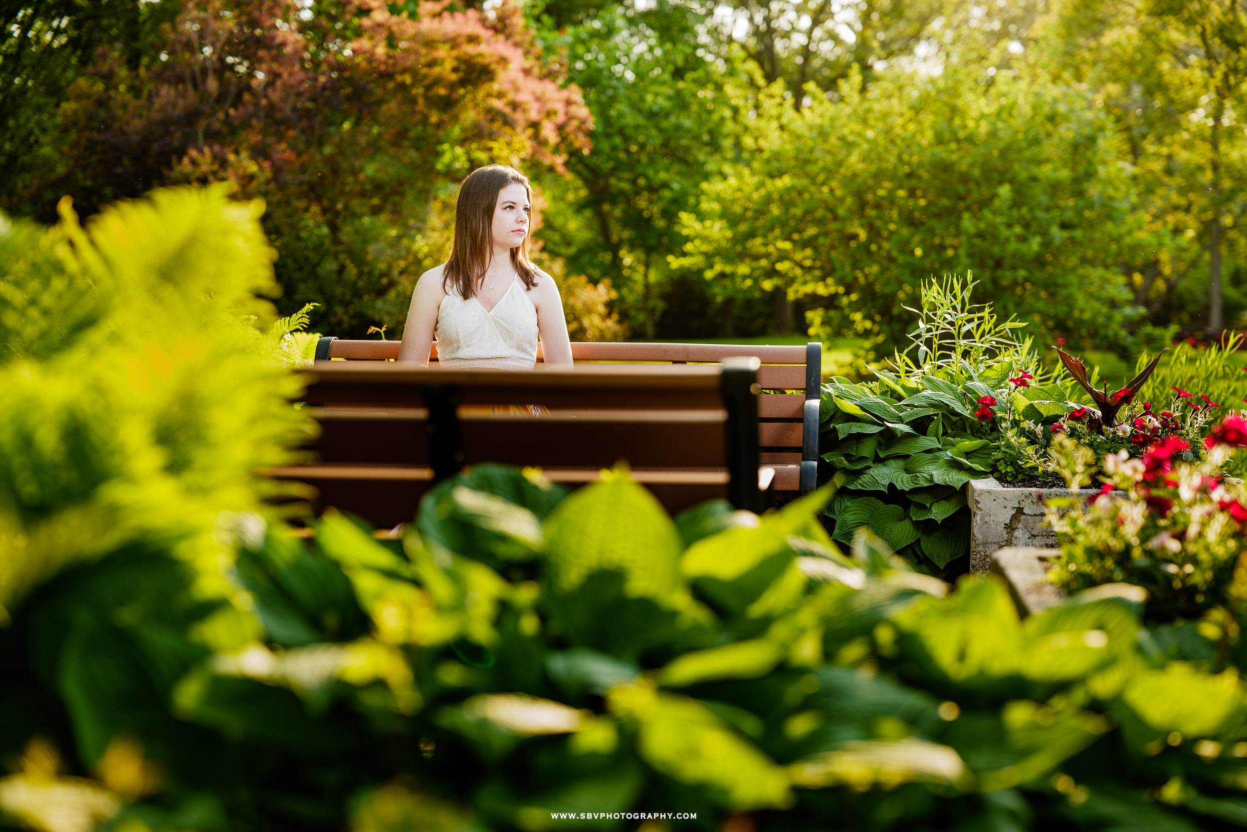 Senior girl sitting on a garden bench in Valparaiso, Indiana.