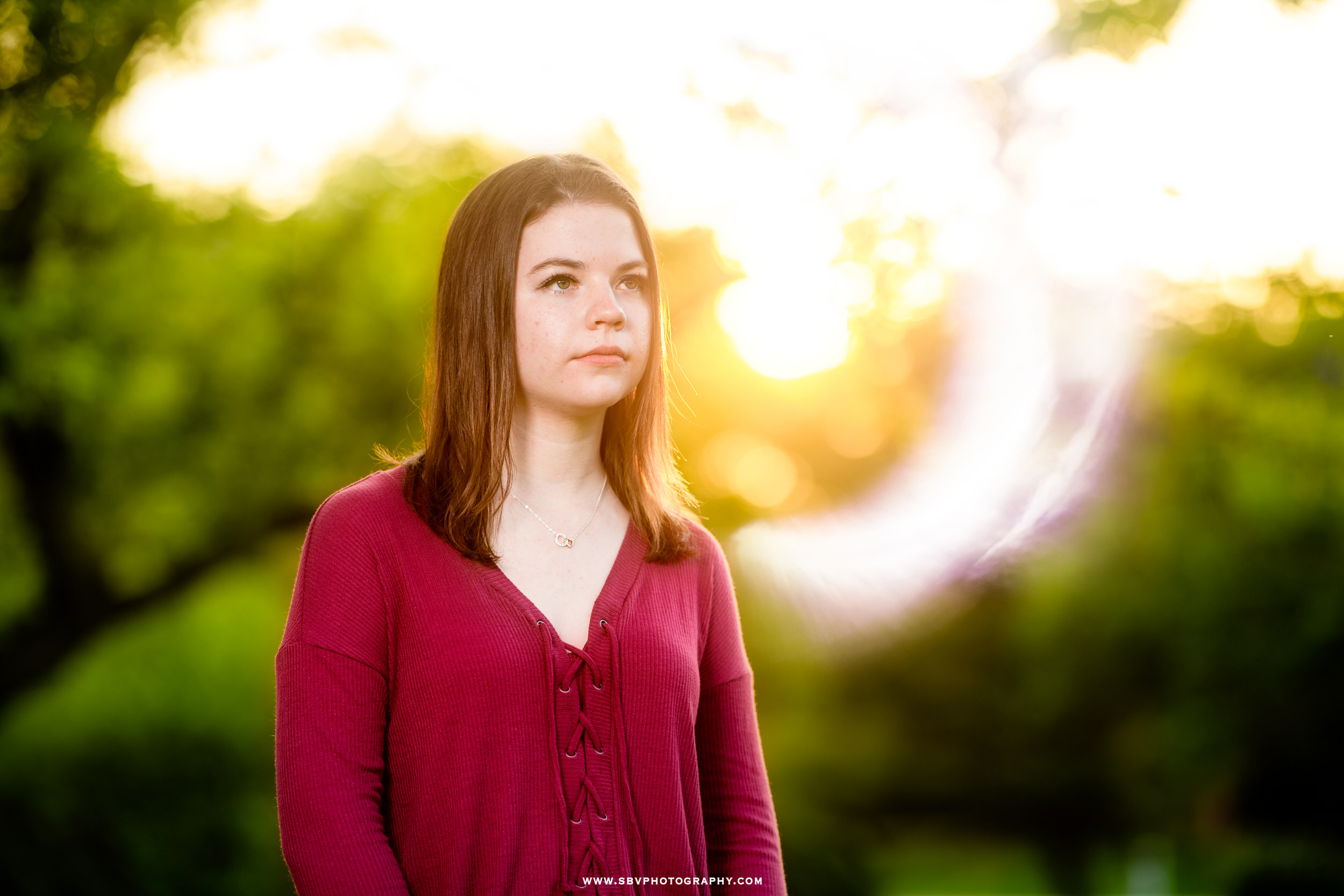 Sun flare surrounds a senior girl for her golden hour portrait.