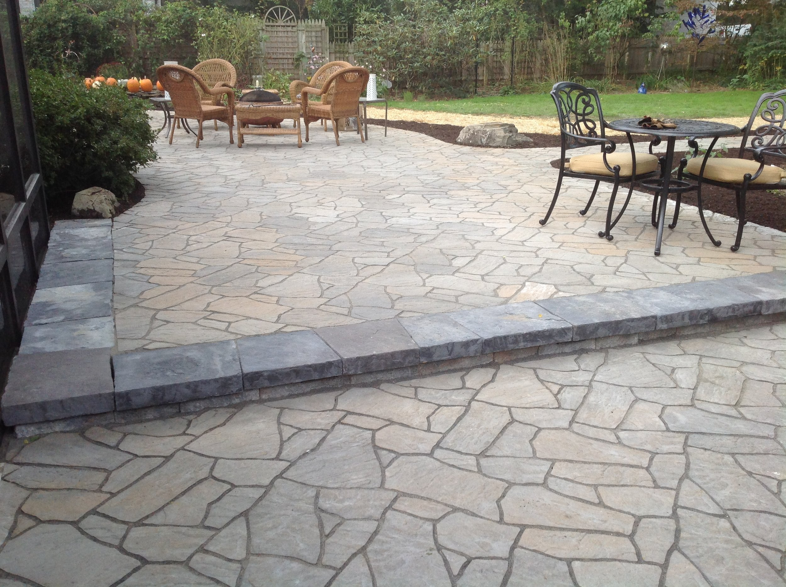 This new patio is made from pavers to resemble flagstone. The raised portion is to help protect the vulnerable tree roots. Lights under the step add safety for evening patio use.