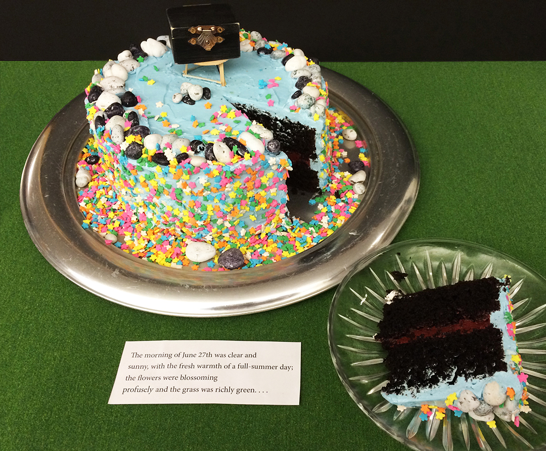 """Two layers of black chocolate cake with blood-red filling and sky blue frosting. Adorned with a """"profuse"""" amount of flower sprinkles, chocolate stones, a hand-made 3-legged stool, and an aged black box containing tiny slips of paper. Before the icing was applied, I slipped one large piece of paper onto which was placed a single smeared dot into the cake; asurprise for one taster."""