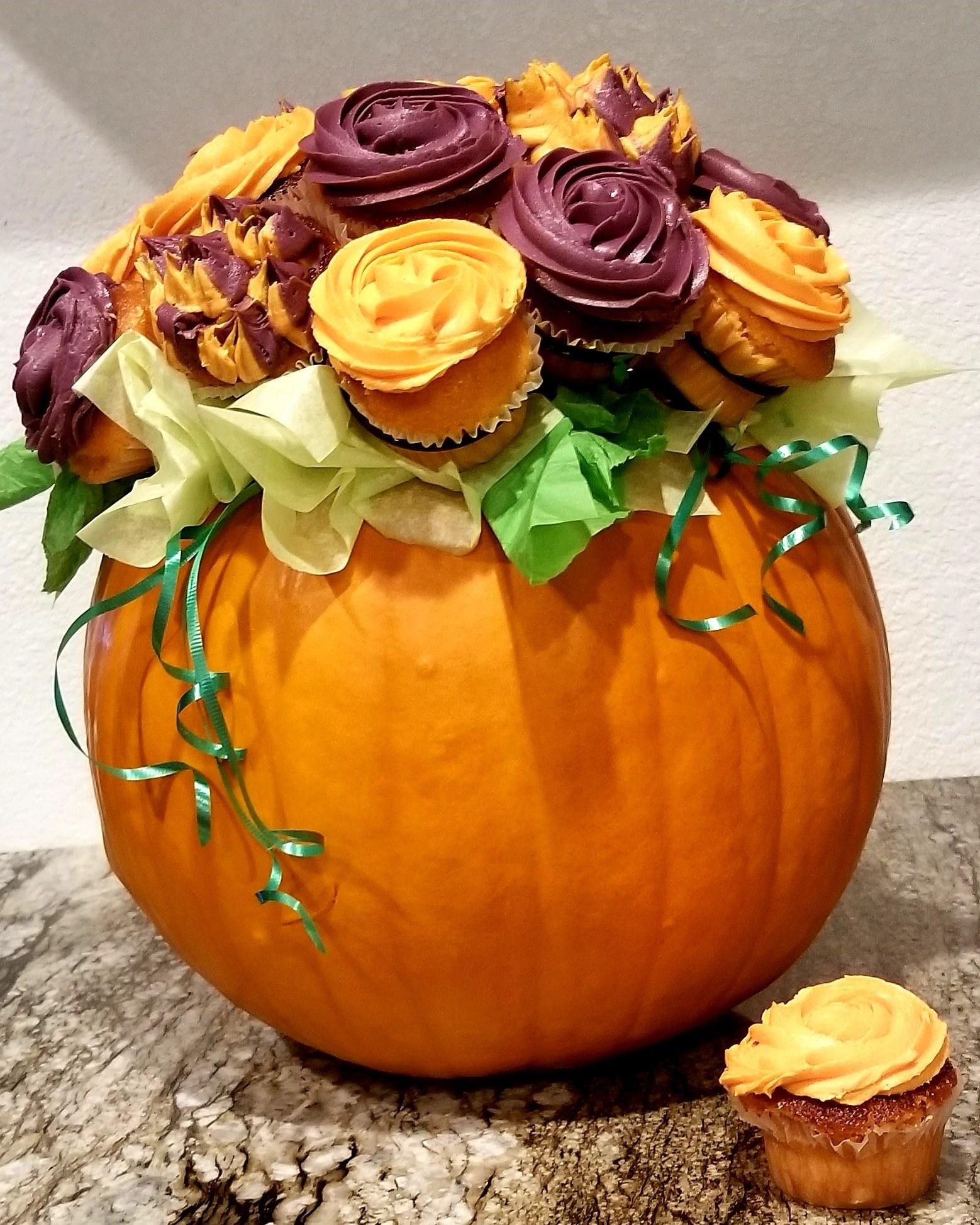 Pumpkin Cupcake Bouquet - Be the talk of the party when you bring along this gorgeous table centerpiece/dessert/hostess gift! Once your friends figure out that your bouquet is made of CUPCAKES, you will have all the attention you desire! This deliciously adorable bouquet is made by carving out a pumpkin, inserting The Cupcake Rack and 19 cupcakes, along with some tissue and ribbon! Easy and oh so beautiful!
