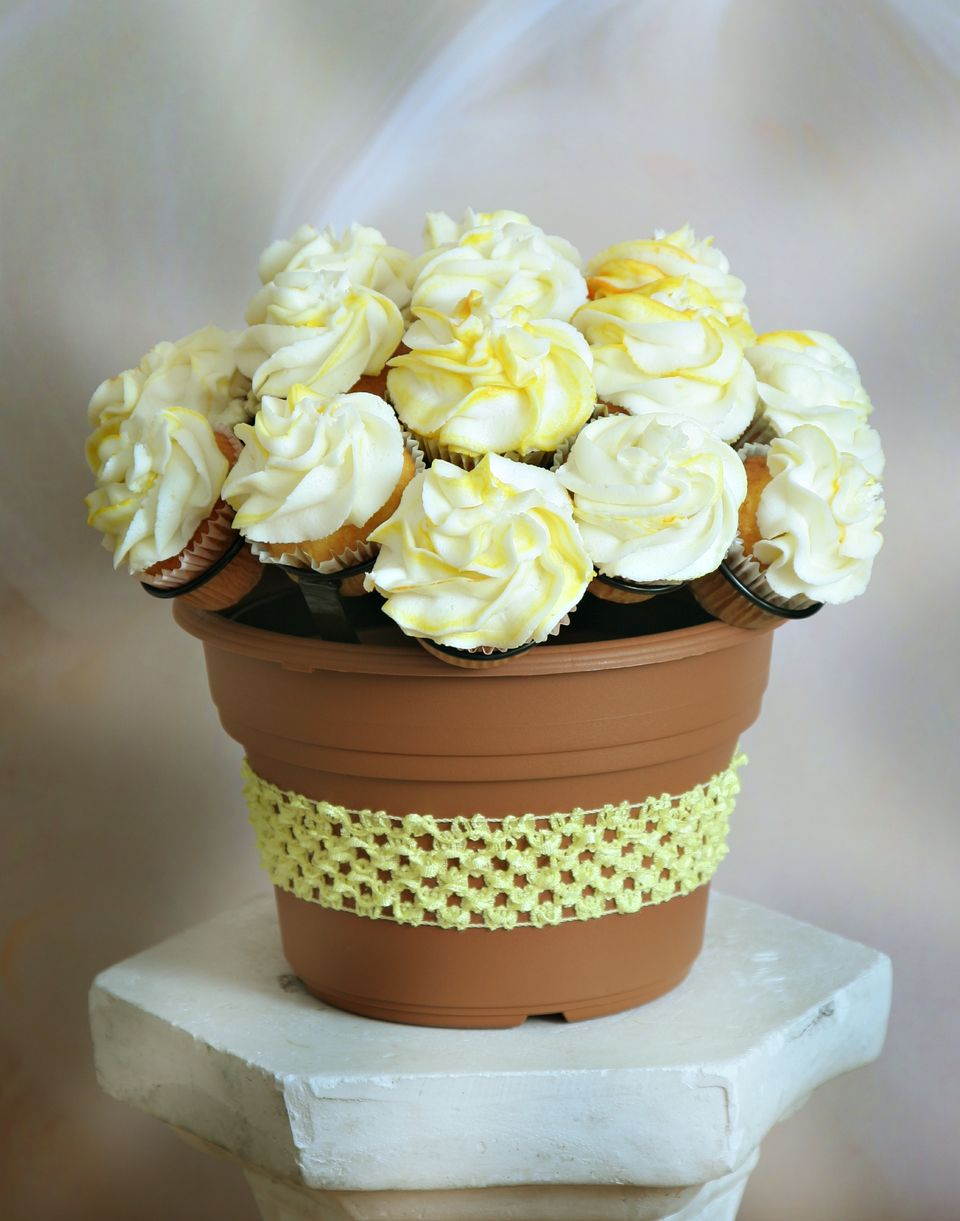Lemony Cupcake Bouquet - Lemon flavored homemade cupcakes swirled with lemony icing with a tinge of yellow coloring is quick and easy to make. Insert your cupcakes into the rings of the rack, place your decorating bag into a tall glass and paint yellow vertical stripes of food coloring up the inside of the bag, then add lemony vanilla frosting into the bag. Using an open star tip, swirl your icing in circles to create the flower look! You can do it!!! Then send us your pics to share on our website and social media! #TastyCupcakeBouquet