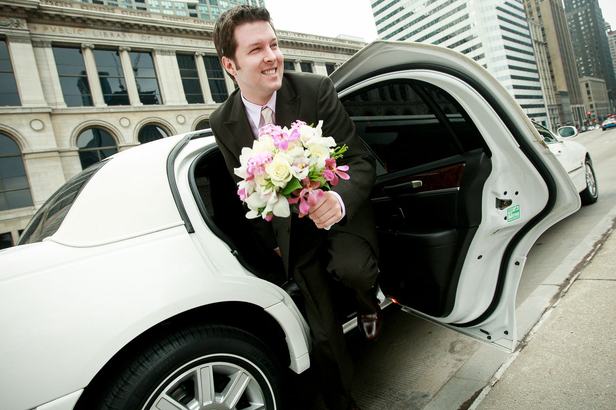 Groom holds the bouquet as he exits the limo at Millennium Park Chicago.