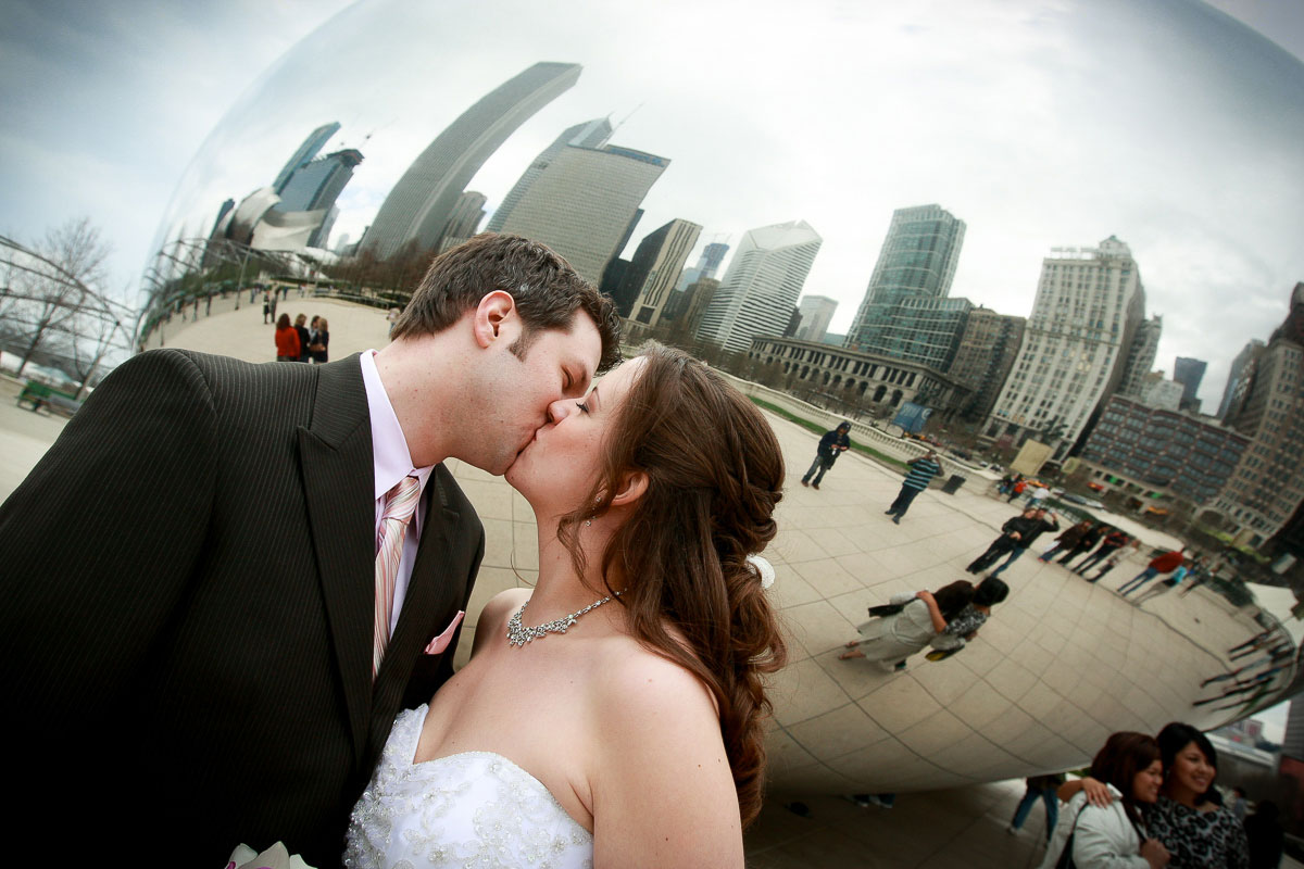 Bride & groom kiss for a portrait in front of the Bean at Millennium Park.
