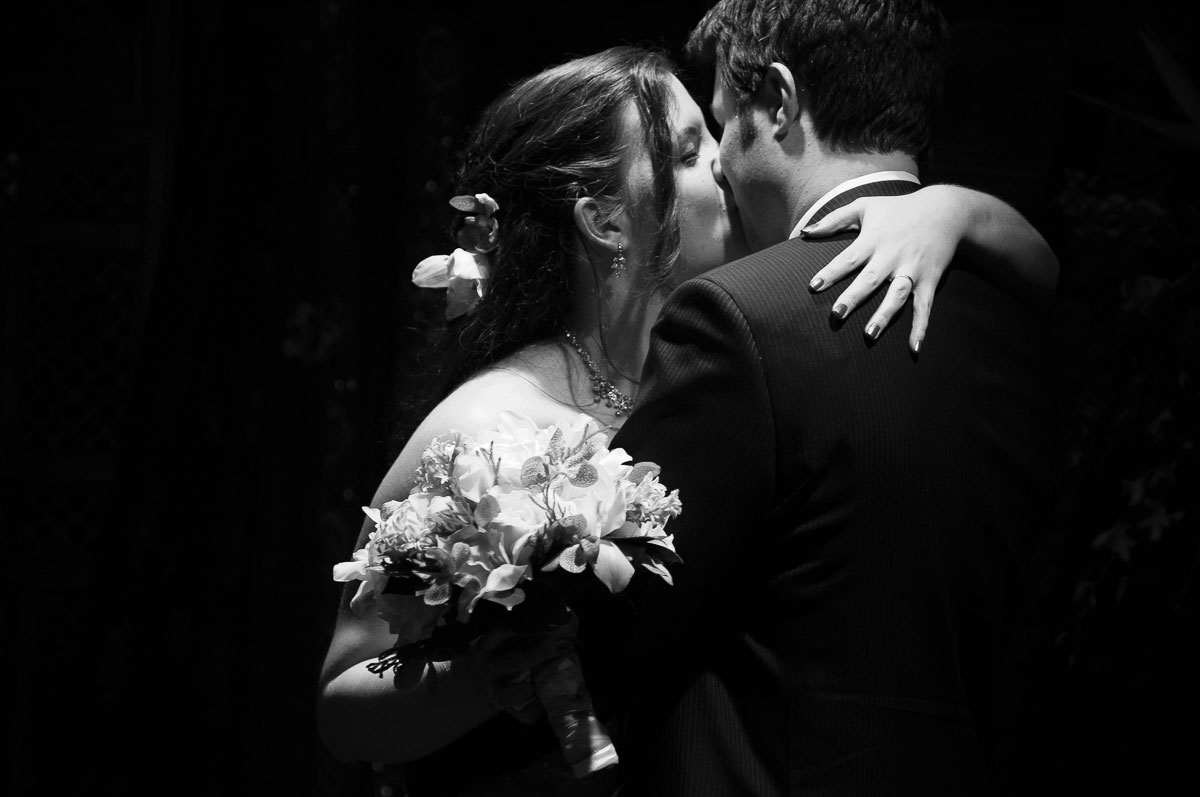 Dramatically lit photo of couple kisses during their Catalyst Ranch wedding ceremony.