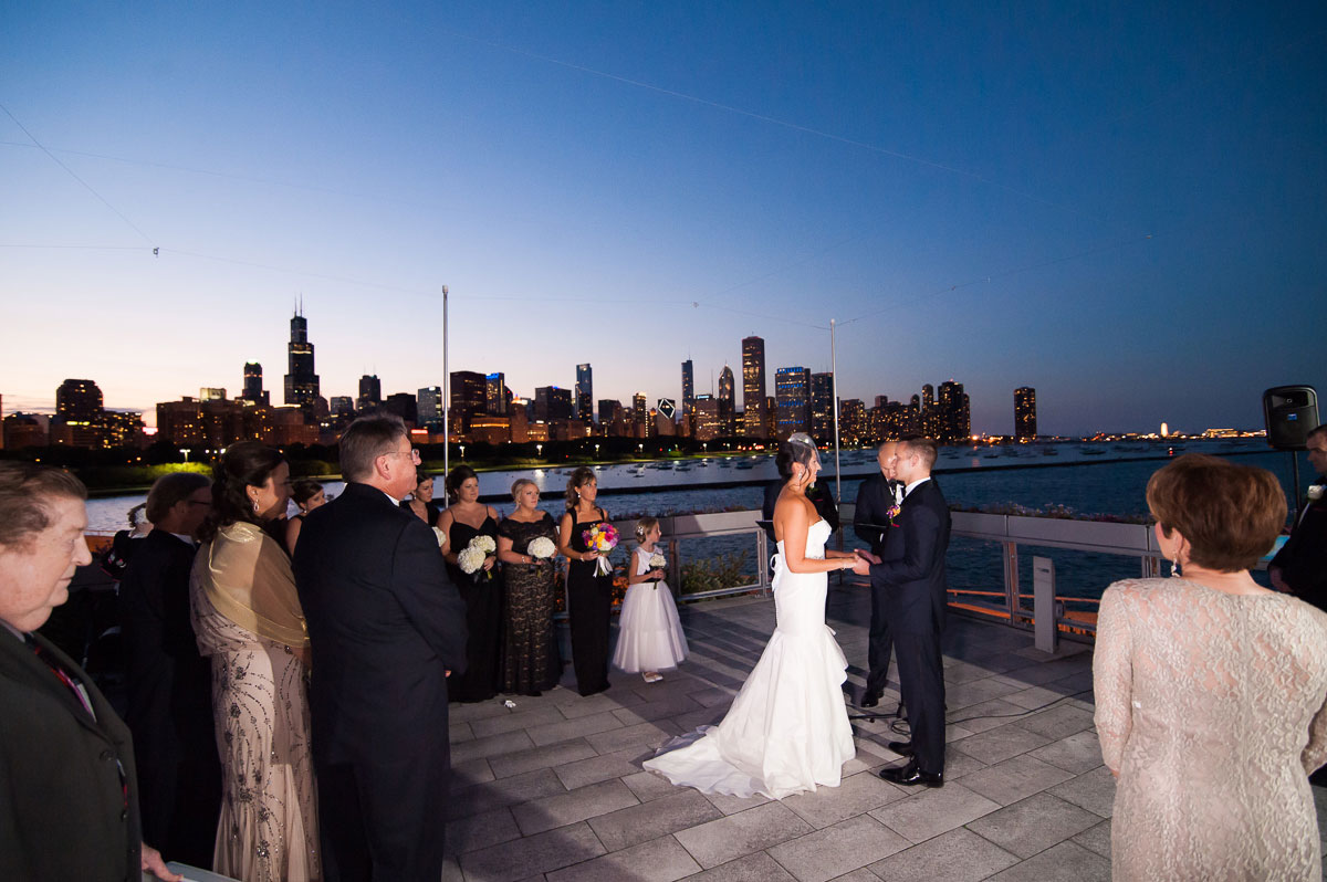 Bride & groom say their vows as the sun sets over the Chicago skyline at the Shedd Aquarium.
