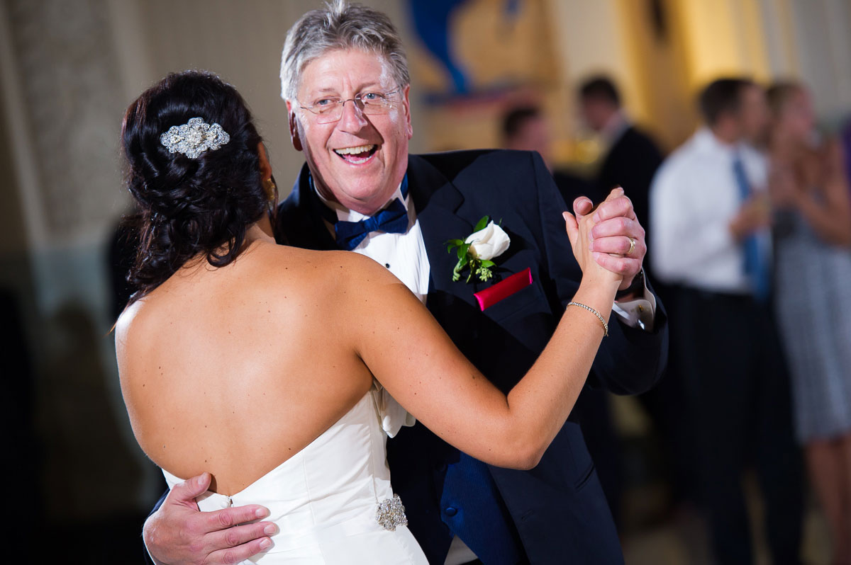 A father laughs with his daughter during their wedding dance at the Shedd Aquarium.