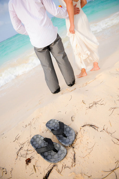 Groom kicks off his sandals to walk on the beach with his bride in Punta Cana.