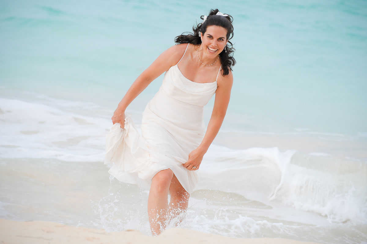 Bride takes a dip in the ocean after her wedding ceremony in Punta Cana.