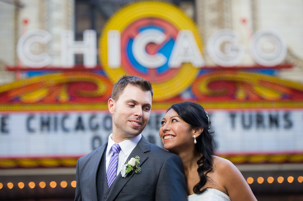 Couple look to each outside the Chicago Theater during their wedding day.