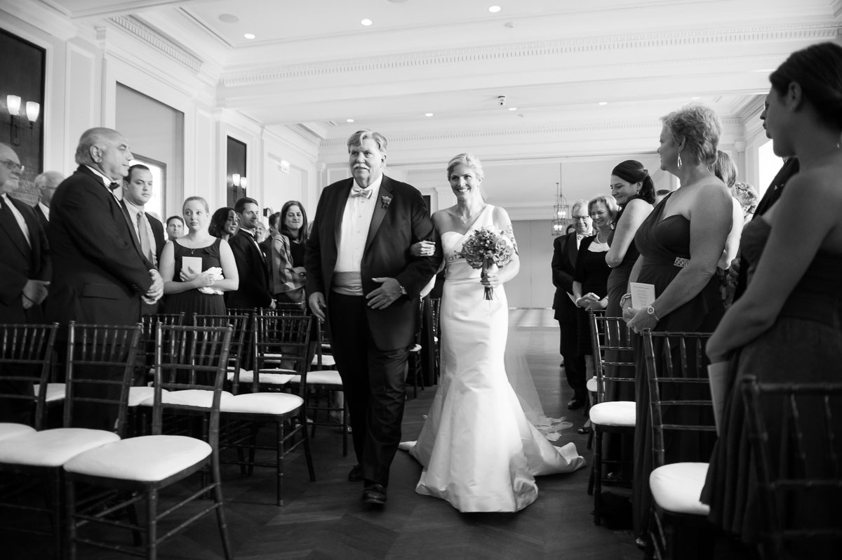 Bride walks down the aisle with her father during her wedding at the Chicago History Museum.