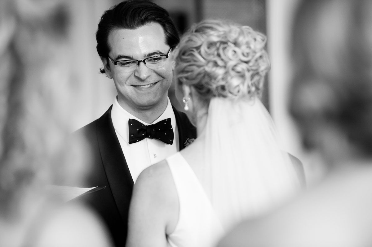 Groom smiles at his bride during their wedding ceremony at the Chicago History Museum.