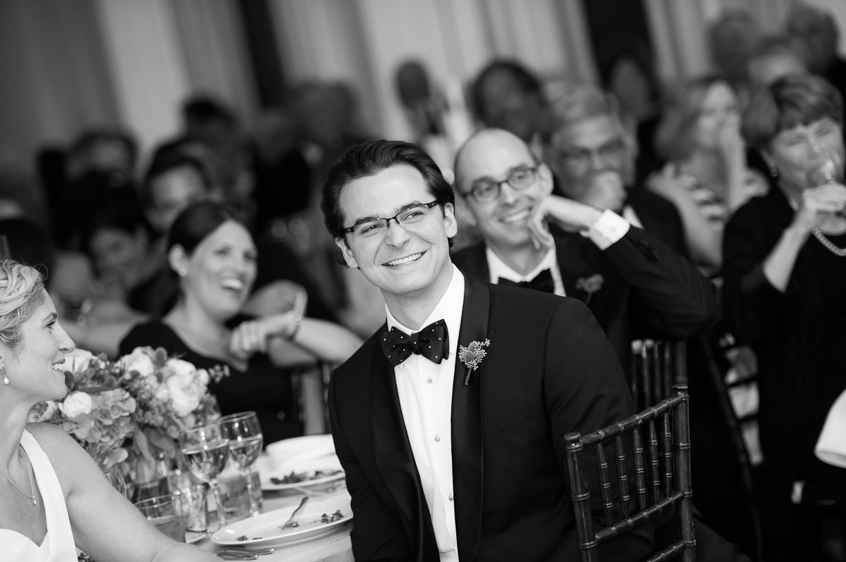 Groom laughs during the best man toast at his Chicago History Museum wedding reception.