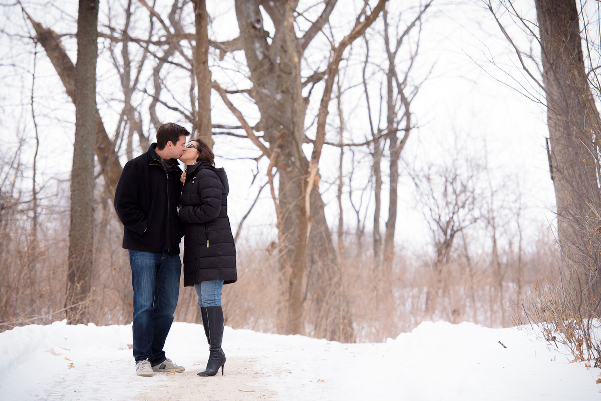 The couple pauses for a kiss during their winter engagement session at Deicke Park in Huntley.